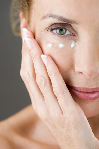 A middle-aged woman applying eye cream